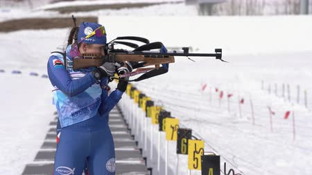 biathlete : Russian sportswomans biathlete aiming, rifle shooting and reloading in standing position. Biathlete shooting range during Junior biathlon competitions East Cup. Kamchatka, Russia - April 13, 2019