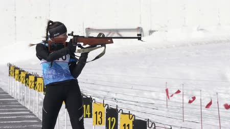 posição : Sportswoman biathlete aiming, rifle shooting, reloading in standing position. Biathlete Elizaveta Knyazeva in shooting range. Junior biathlon competitions East of Cup. Kamchatka, Russia - Apr 13, 2019
