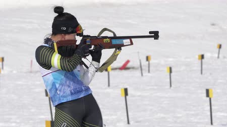 biathlete : Sportswoman biathlete aiming, rifle shooting, reloading standing position. South Korea biathlete Lee Hyunju in shooting range. Junior biathlon competitions East Cup. Kamchatka, Russia - April 13, 2019