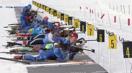 biathlon : Group sportswoman biathlete aiming, rifle shooting, reloading rifle in prone position. Biathletes in shooting range. Regional junior biathlon competitions East Cup. Kamchatka, Russia - April 13, 2019.