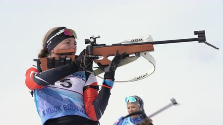 gunshot : Sportswoman biathlete aiming, rifle shooting, reloading in standing position. Biathlete Eremeeva Elizaveta in shooting range. Junior biathlon competitions East Cup. Kamchatka, Russia - April 13, 2019 Stock Footage