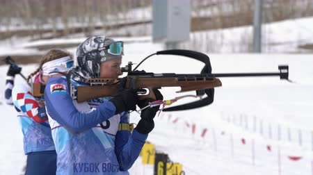 biathlon : Sportswoman biathlete aiming, rifle shooting standing position. Biathlete Arina Soldatova in shooting range. Regional junior biathlon competitions East Cup. Kamchatka Peninsula, Russia - Apr 13, 2019.
