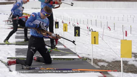 biathlete : Group of sportsman biathlete rifle shooting in shooting range. Regional junior biathlon competitions East of Cup. Petropavlovsk-Kamchatsky City, Kamchatka Peninsula, Russian Far East - April 13, 2019. Stock Footage