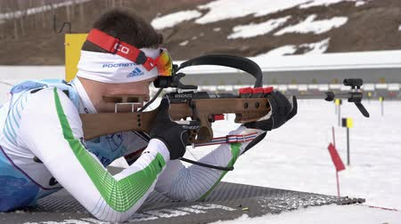 russian far east : Sportsman biathlete aiming, rifle shooting, reloading rifle in prone position. Biathlete Zlobin Vladislav in shooting range. Junior biathlon competitions East Cup. Kamchatka, Russia - April 13, 2019