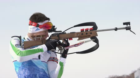 biathlete : Sportsman biathlete aiming, rifle shooting, reloading rifle in standing position. Biathlete Vladislav Zlobin in shooting range. Junior biathlon competitions East Cup. Kamchatka, Russia - Apr 13, 2019 Stock Footage