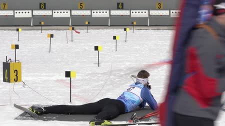 prone position : Sportsman biathlete aiming, rifle shooting, reloading rifle in prone position. Biathlete Ageev Danil in shooting range during Junior biathlon competitions East Cup. Kamchatka, Russia - April 13, 2019. Stock Footage