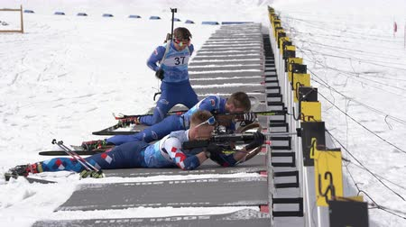 biathlete : Group of sportsman biathlete aiming, rifle shooting, reloading rifle in prone position during Regional junior biathlon competitions East of Cup. Kamchatka Peninsula, Russian Far East - April 13, 2019.