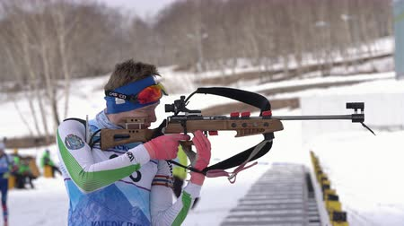 posição : Sportsman biathlete aiming, rifle shooting, reloading rifle in standing position. Biathlete Rusinov Vladislav in shooting range. Junior biathlon competitions East Cup. Kamchatka, Russia - Apr 13, 2019