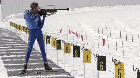 biathlete : Junior biathlon competitions East of Cup. Sportsman biathlete aiming, rifle shooting, reloading rifle in standing position. Biathlete Agin Pavel in shooting range. Kamchatka, Russia - April 13, 2019