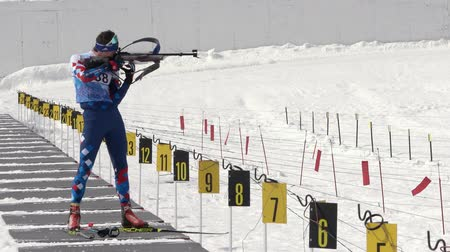 posição : Sportsman biathlete aiming, rifle shooting, reloading rifle in standing position. Junior biathlon competitions East Cup. Biathlete Artem Amirbekov in shooting range. Kamchatka, Russia - April 13, 2019