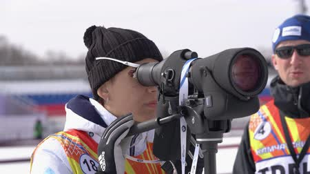 biathlete : Coach Aksenova Olesya Aleksandrovna Saint Petersburg watches biathletes in monocle at shooting range of biathlon arena. Regional Junior biathlon competitions East Cup. Kamchatka, Russia - Apr 13, 2019