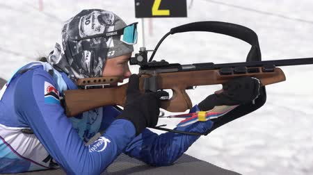 golyó : Sportswoman biathlete aiming, rifle shooting prone position. Kamchatka biathlete Arina Soldatova in shooting range. Regional junior biathlon competitions East Cup. Kamchatka, Russia - April 13, 2019.