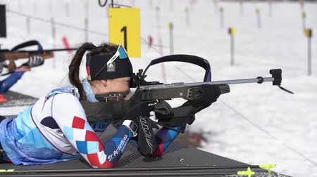 prone position : Sportswoman biathlete aiming, rifle shooting in prone position. Biathlete Vlada Shishkina Saint Petersburg in shooting range. Junior biathlon competitions East Cup. Kamchatka, Russia - April 13, 2019.