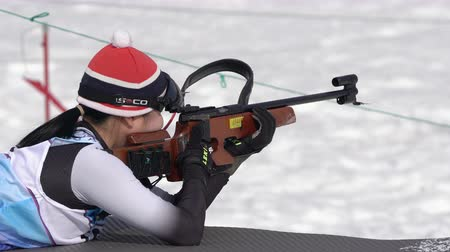 prone position : Sportswoman biathlete aiming, rifle shooting prone position. South Korea biathlete Choi Yoonah in shooting range. Junior biathlon competitions East of Cup. Kamchatka Peninsula, Russia - April 13, 2019