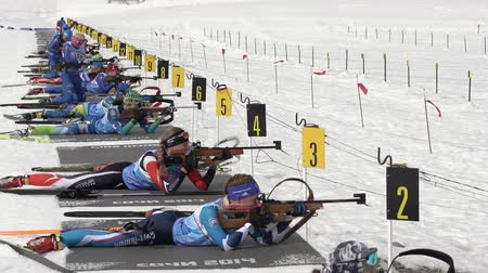 prone position : Group of sportswoman biathlete aiming, rifle shooting in prone position on shooting range biathlon arena. Junior biathlon competitions East Cup. Petropavlovsk City Kamchatka, Russia - April 13, 2019. Stock Footage