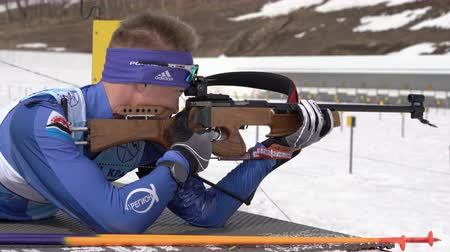 prone position : Sportsman biathlete aiming, rifle shooting, reloading rifle in prone position. Biathlete Kozulin Aleksander in shooting range. Junior biathlon competitions East Cup. Kamchatka, Russia - April 13, 2019