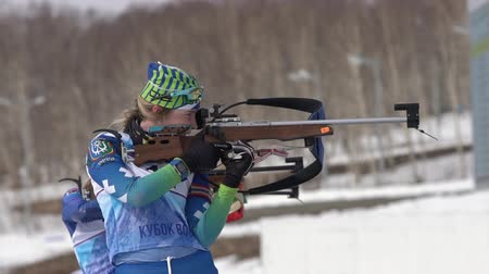 golyó : Sportswoman biathlete aiming, rifle shooting in standing position. Kamchatka biathlete Legostaeva Anastasia in shooting range. Junior biathlon competitions East Cup. Kamchatka, Russia - April 13, 2019 Stock mozgókép