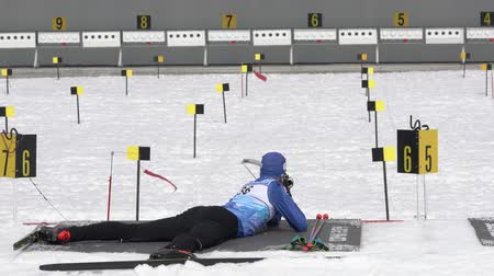 uzak : Sportsman biathlete aiming, rifle shooting, reloading rifle in prone position. Biathlete Smolyakov Danila in shooting range. Junior biathlon competitions East Cup. Kamchatka, Russia - April 13, 2019. Stok Video