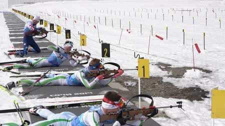 biathlon : Group of sportsman biathlete rifle shooting, aiming, reloading rifle in prone position. Junior biathlon competitions East of Cup. Petropavlovsk, Kamchatka Peninsula, Russian Far East - April 13, 2019.