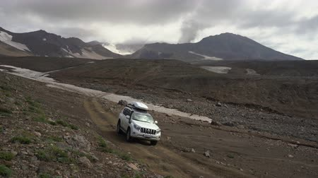 daleko : Japanese SUV Toyota Land Cruiser Prado driving on mountain road in direction of popular travel destinations for mountain climbing - active Mutnovsky Volcano. Kamchatka Peninsula, Russia - Aug 16, 2019