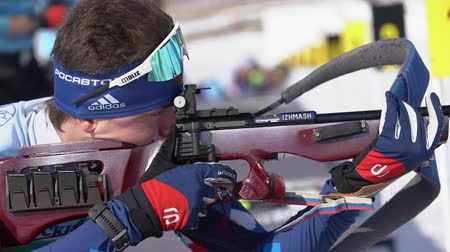 uzak : Sportsman biathlete rifle shooting, aiming, reloading rifle in prone position. Biathlete Amirbekov Artem in shooting range. Junior biathlon competitions East of Cup. Kamchatka, Russia - April 14, 2019 Stok Video