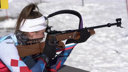 biathlete : Sportswoman biathlete aiming, rifle shooting in prone position. Biathlete Petrova Victoria Saint Petersburg in shooting range. Junior biathlon competitions East Cup. Kamchatka, Russia - April 14, 2019