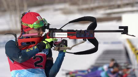 kurşun : Sportswoman biathlete aiming, rifle shooting, reloads standing position. Biathlete Polina Yegorova Kazakhstan in shooting range. Junior biathlon competitions East Cup. Kamchatka, Russia - Apr 14, 2019 Stok Video