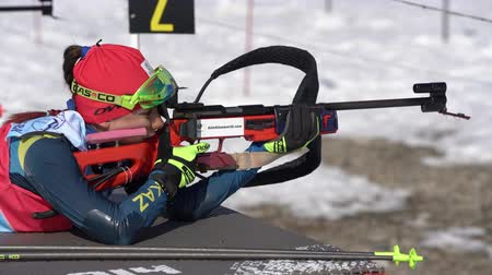 golyó : Sportswoman biathlete aiming, rifle shooting, reloading prone position. Kazakhstan biathlete Polina Yegorova in shooting range. Junior biathlon competitions East Cup. Kamchatka, Russia - Apr 14, 2019. Stock mozgókép