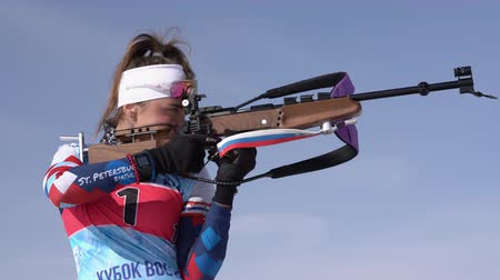 aim : Sportswoman biathlete aiming, rifle shooting standing position. Biathlete Petrova Victoria Saint Petersburg in shooting range. Junior biathlon competitions East Cup. Kamchatka, Russia - April 14, 2019