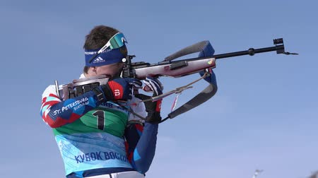 gunshot : Sportsman biathlete aiming, rifle shooting in standing position. Junior biathlon competitions East Cup. Saint Petersburg biathlete Amirbekov Artem in shooting range. Kamchatka, Russia - April 14, 2019