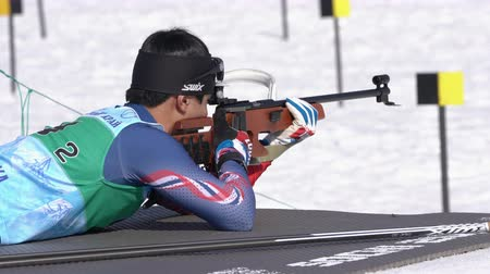 biathlete : Sportsman biathlete aiming, rifle shooting, reloads in prone position. South Korea biathlete Yang Seon Jik in shooting range. Junior biathlon competitions East of Cup. Kamchatka, Russia - Apr 14, 2019 Stock Footage