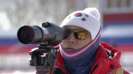 russian far east : Coach of South Korea biathlon team watches biathletes in monocle at shooting range of biathlon arena. Junior biathlon competitions East of Cup. Kamchatka Peninsula, Russian Far East - April 14, 2019 Stock Footage