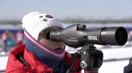 biathlete : Coach of South Korea biathlon team watches biathletes in monocle at shooting range of biathlon stadium. Junior biathlon competitions East of Cup. Petropavlovsk City Kamchatka, Russia - April 14, 2019 Stock Footage