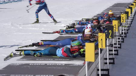 prone position : Sportswoman biathletes in shooting range stadium. Group biathlete aiming, rifle shooting, reloading rifle in prone position. Junior biathlon competitions East of Cup. Kamchatka, Russia - Apr 14, 2019