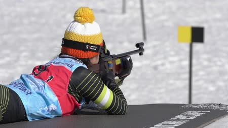 biathlete : Sportswoman biathlete aiming, rifle shooting in prone position. Biathlete Lee Hyunju South Korea in shooting range. Junior biathlon competitions East Cup. Kamchatka Peninsula, Russia - April 14, 2019.