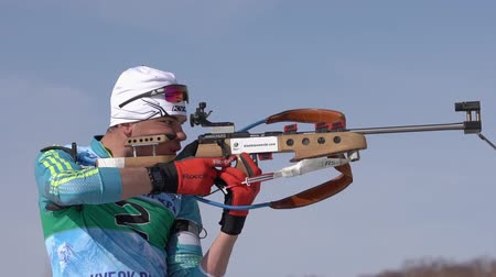 biathlon : Sportsman biathlete aiming, rifle shooting in standing position. Junior biathlon competitions East of Cup. Kazakhstan biathlete Kireyev Vladislav in shooting range. Kamchatka, Russia - April 14, 2019. Stock Footage