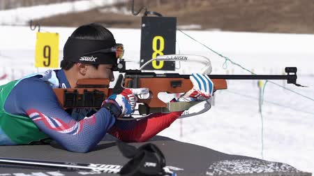 prone position : Sportsman biathlete aiming, rifle shooting, reloading rifle in prone position. Yang Seon Jik South Korea in shooting range. Junior biathlon competitions East Cup. Kamchatka, Russia - Apr 14, 2019