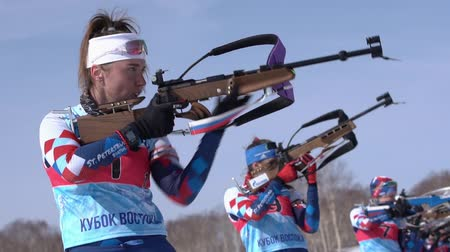 reloading : Biathlete Victoria Petrova Saint Petersburg in shooting range. Sportswoman biathlete aiming, rifle shooting standing position. Junior biathlon competitions East Cup. Kamchatka, Russia - April 14, 2019 Stock Footage