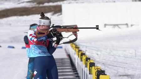 reloading : Sportswoman biathlete aiming, rifle shooting standing position. Biathlete Labutina Anna in shooting range. Junior biathlon competitions East Cup. Petropavlovsk City, Kamchatka, Russia - April 14, 2019