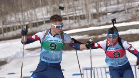biathlon : Saint Petersburg team sportsman biathletes Zaytsev Aleksander and Yashunkina Yuliya skiing snow ski track relay race Junior biathlon competitions East Cup. Kamchatka Peninsula, Russia - April 14, 2019