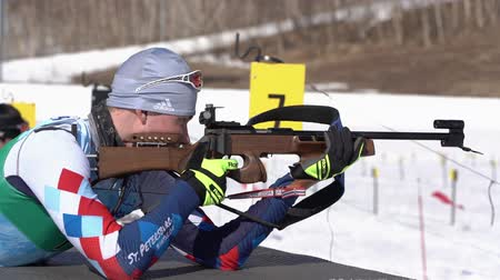 gunshot : Sportsman biathlete aiming, rifle shooting, reloading rifle in prone position. Biathlete Roduner Dionis in shooting range. Junior biathlon competitions East of Cup. Kamchatka, Russia - April 14, 2019