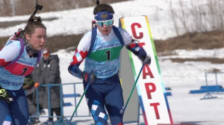 biathlete : Saint Petersburg team sportsman biathletes Amirbekov Artem and Petrova Victoria skiing snow ski track relay race Junior biathlon competitions East of Cup. Kamchatka Peninsula, Russia - April 14, 2019.