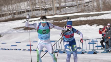 sztafeta : Khanty-Mansiysk team sportsman biathletes Ziganchin Rafael and Hairulina Elena skiing snow ski track relay race Junior biathlon competitions East of Cup. Kamchatka Peninsula, Russia - April 14, 2019.