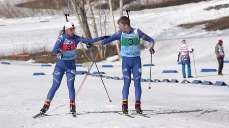 staffetta : Kamchatka team sportsman biathletes Smolyakov Danila and Miroshnichenko Maria skiing snow ski track relay race Junior biathlon competitions East of Cup. Kamchatka Peninsula, Russia - April 14, 2019.