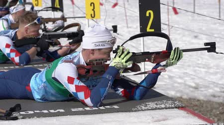 gunshot : Sportsman biathlete aiming, rifle shooting, reloading rifle in prone position. Biathlete Akhtyamov Ilmir in shooting range. Junior biathlon competitions East of Cup. Kamchatka, Russia - April 14, 2019 Stock Footage
