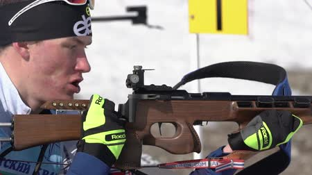 golyó : Junior biathlon competitions East of Cup. Sportsman biathlete aiming, rifle shooting, reloading rifle in prone position. Biathlete Dionis Roduner in shooting range. Kamchatka, Russia - April 14, 2019 Stock mozgókép