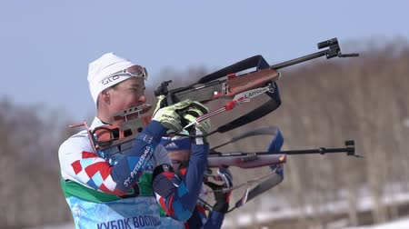 posição : Sportsman biathlete aiming, rifle shooting and reloading in standing position. Biathlete Ilmir Akhtyamov in shooting range. Junior biathlon competitions East of Cup. Kamchatka, Russia - April 14, 2019
