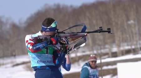 biathlete : Sportsman biathlete aiming, rifle shooting and reloading in standing position. Biathlete Amirbekov Artem in shooting range. Junior biathlon competitions East of Cup. Kamchatka, Russia - April 14, 2019 Stock Footage