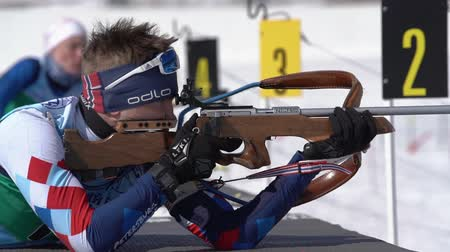 gunshot : Biathlete aiming, rifle shooting, reloading rifle in prone position. Sportsman biathlete Khmara Yaroslav in shooting range. Junior biathlon competitions East of Cup. Kamchatka, Russia - April 14, 2019
