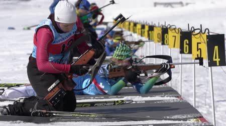 gunshot : Group sportswoman biathlete aiming, rifle shooting, reloading rifle in prone position. Biathletes in shooting range stadium. Junior biathlon competitions East of Cup. Kamchatka, Russia - Apr 14, 2019